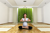 A young woman in the yoga lotus position — Stock Photo