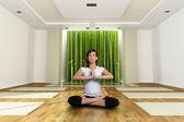 Una giovane donna nella posizione del loto yoga — Foto Stock