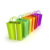 Brightly colored shopping bags in a row — Stock Photo