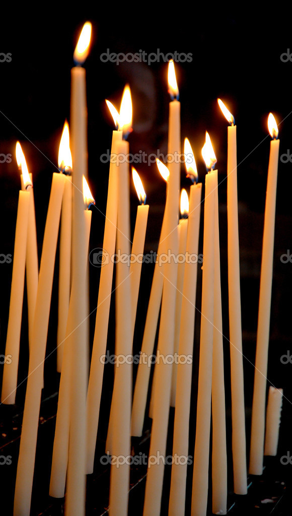 Church candles lit against black background  Stock Photo #2456435
