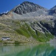 Stock Photo: Alpine lake and mountain hut