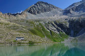 Alpine lake and mountain hut — Stock Photo