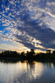 Cloudscape at sunset over a lagoon — Foto Stock