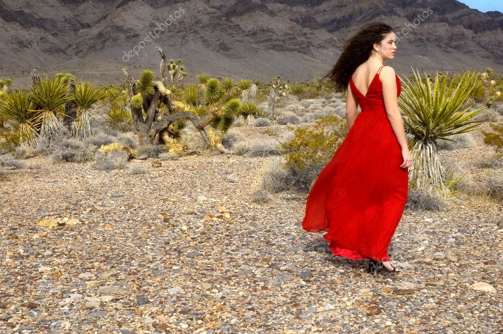 A girl walking in the desert wearing a red silk evening gown and stilettos — Stock Photo #2222980