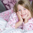 Stock Photo: Cute Blonde Child Lying on her Bed