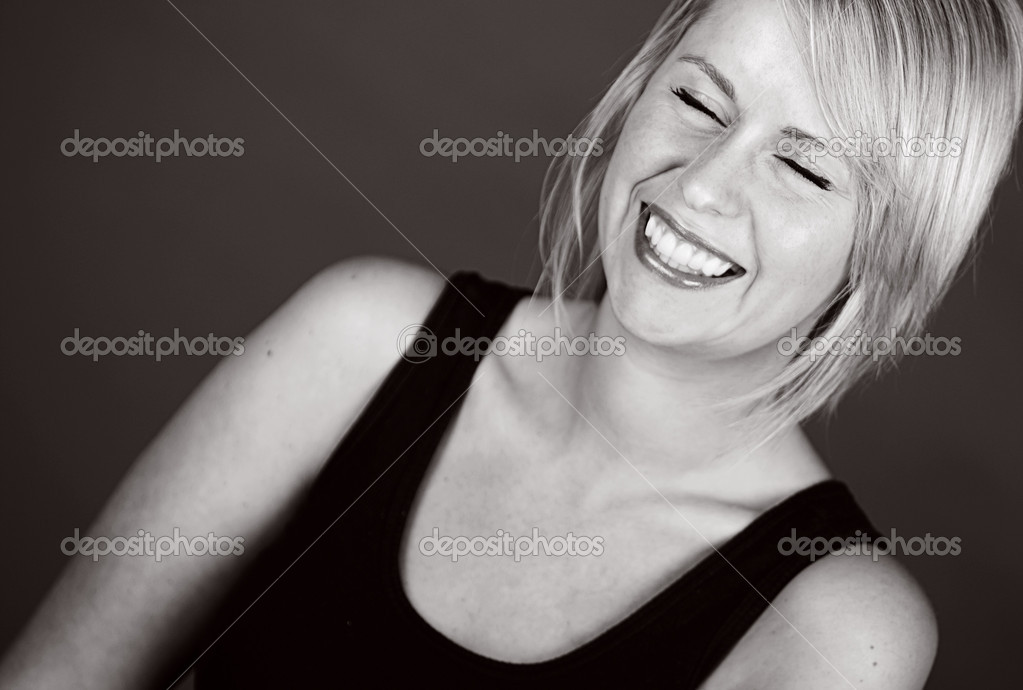 Shot of a Beautiful Smiling Blonde Girl against Dark Background — Stock Photo #2338341