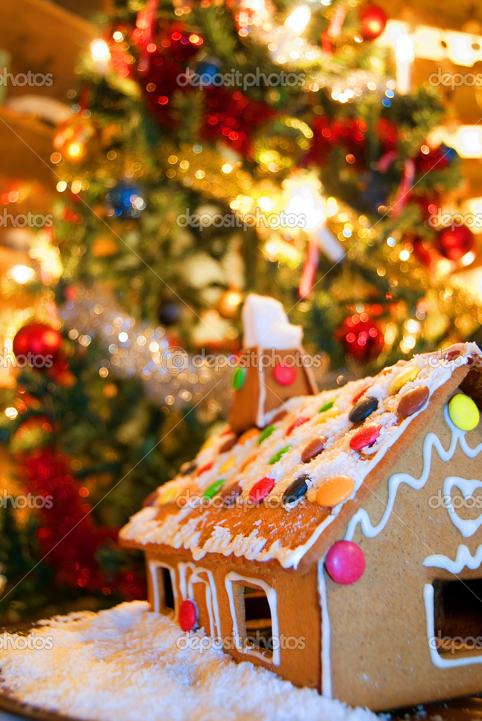 A tasty looking gingerbread house in front of a highly decorated and colourful christmas tree. — Stock Photo #2300230
