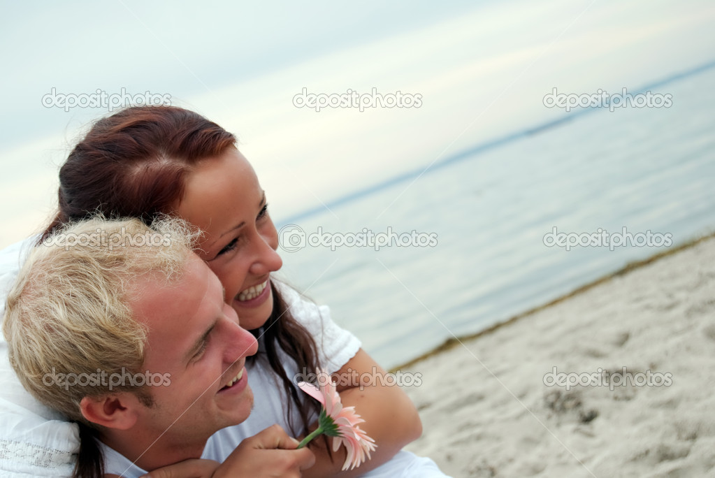 A young woman embraces her lover on a romantic beach setting. — Stock Photo #2492050