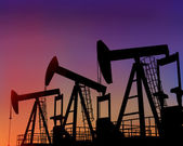 Three oil wells in the desert at dusk — Stock Photo