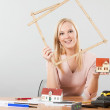 Architect woman holding exposing house — Stock Photo