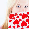 Foto Stock: Young blond womwith valentine card