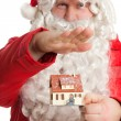 Santa Claus holding house — Stock Photo