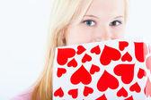 Jonge blonde vrouw met valentine card — Stockfoto