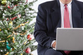 Businessman with pc by christmas tree — Stock Photo