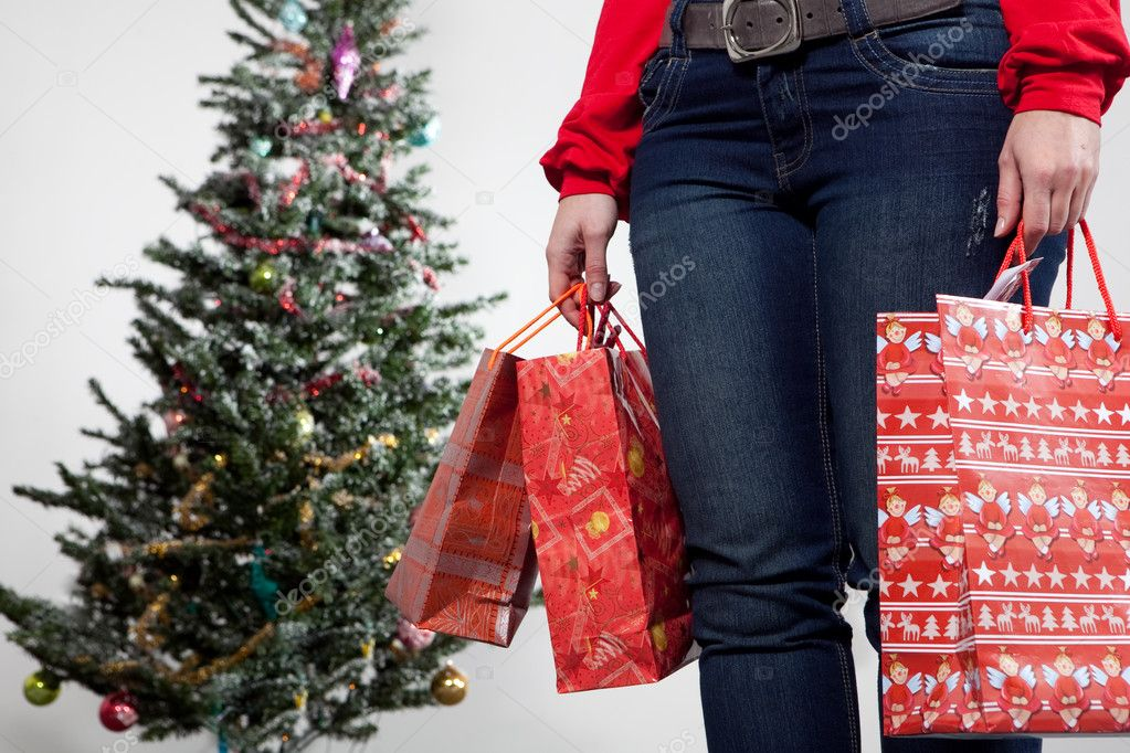 Young adult woman holding bags with christmas bags in front of chirstmas tree — Stock Photo #2511322