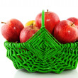 Red apples in green basket — Stock Photo