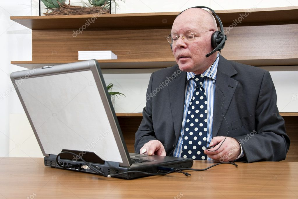 A company director listening to information whilst using his laptop — Photo #2235768
