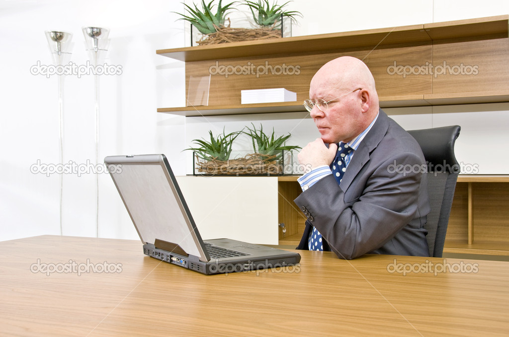 A company director checking information on his laptop — Stock Photo #2237190