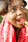Woman with red scarf eating a strawberry — Stock Photo