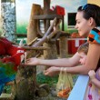 Stock Photo: Mum and daughter feed parrot