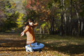 Girl it plays by leaves — Stock Photo