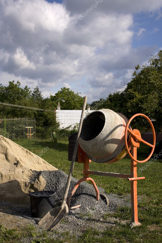Mixer and shovel by a pile of sand — Stock Photo #2234824