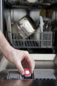 Putting tab into dishwasher — Stock Photo