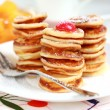 Sweet mini pancakes with pancake maker - Stock Photo