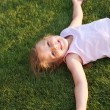 Stock Photo: Happy girl relaxing on a grass