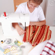 Elderly woman sewing - Stock Photo