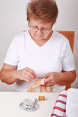 Elderly woman sewing — Stock Photo
