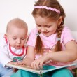 Adorable kids reading and playing - Stock Photo