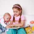 Adorable kids reading and playing — Stock Photo