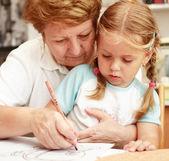 Grandma and grand-daughter painting — Stock Photo