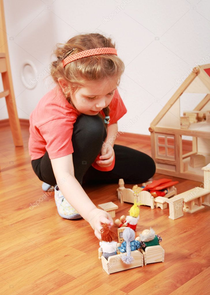 Cute little girl plays with doll's house — Stock Photo #2335370