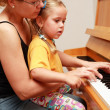 Stock Photo: Mother and daughter play piano