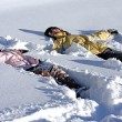 Mother and Daughter laying in the Snow - Stock Photo