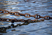 Old rusty chains and sea waves — Stock Photo