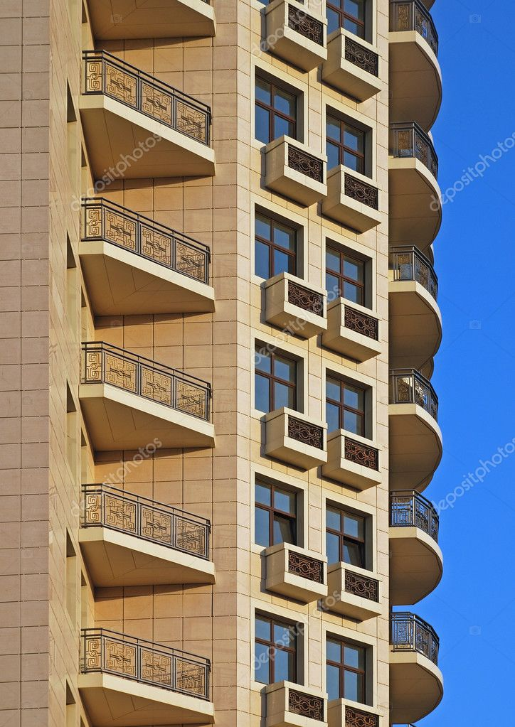 Balcony rows fragment of tall residential building in warm sunset light with beautiful blue sky  Stock Photo #2547713