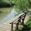 Vacant Park Bench in Front of a River - Stock Photo
