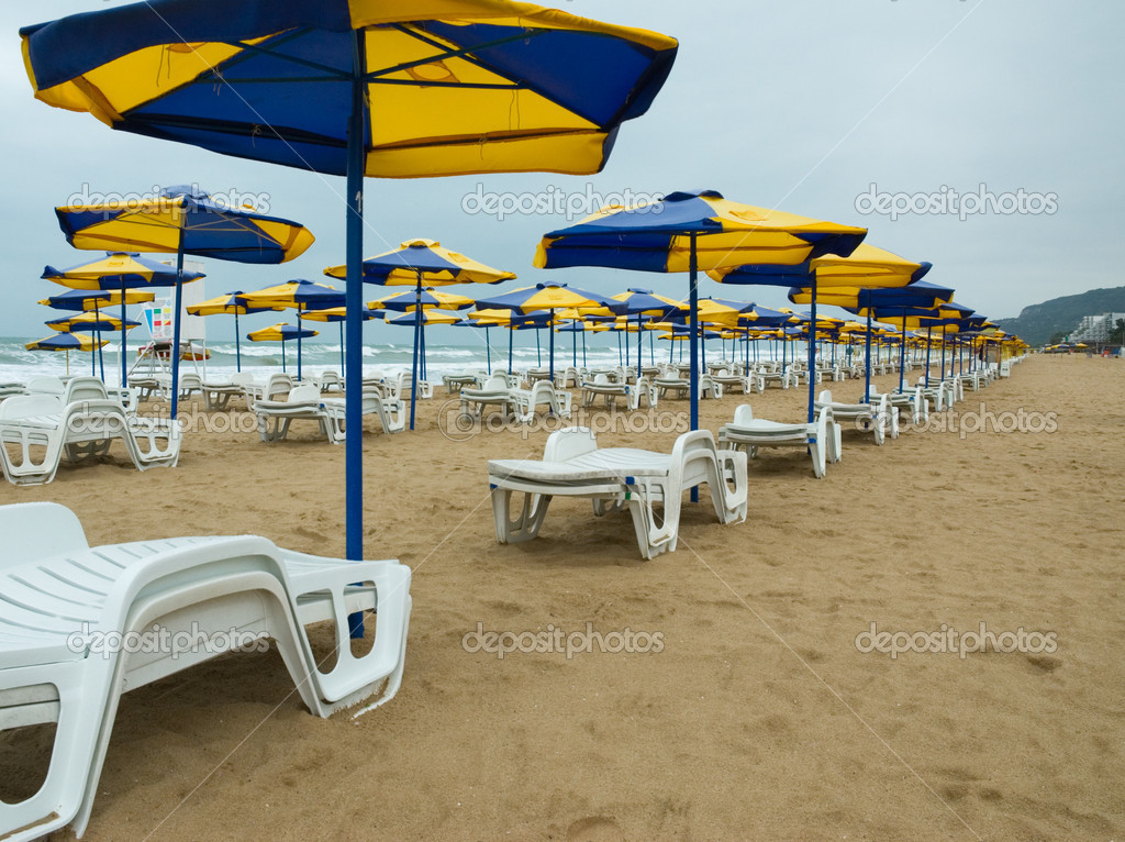 Umbrellas and sunchairs lined up on a low season Black Sea beach — Stock Photo #2570400