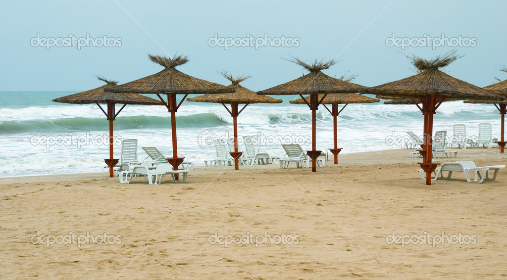 Sunchairs and grass-top umbrellas lined up on a low season Black Sea beach — Stock Photo #2570402