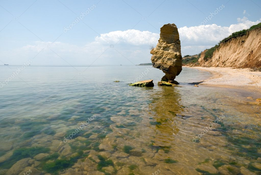 Fantastic rock next to the shoreline of the Black Sea. Sandy beach with steeps. Serene summer midday.  Stock Photo #2570516