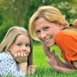 Young mother and daughter laying - Stock Photo