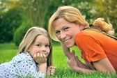 Young mother and daughter laying — Stock Photo