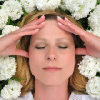 Young woman laying in flowers — Stock Photo