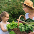 Young woman and daughter with vegetable — Stock Photo