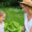 Young mother and daughter with lettuce — Stock Photo #2282245