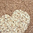 Oats seeds and oat-flakes heart — Stock Photo