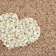 Oats seeds and oat-flakes heart — Stock Photo #2461846